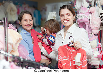 Two women and child at clothes store - Two women and child...