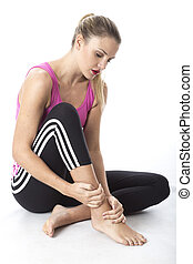 Model Released.  Young Woman Nursing Injured Ankle
