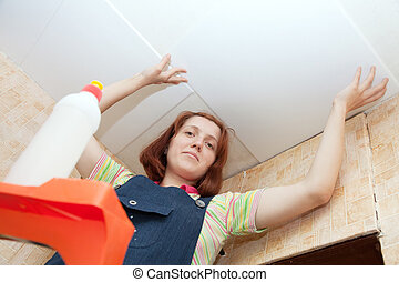 woman glues ceiling tile at home - Young woman glues ceiling...