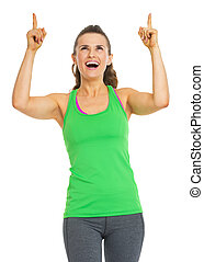 Smiling fitness young woman pointing up on copy space