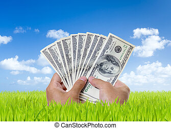 Man hands holding hundred dollar bills on green field with...