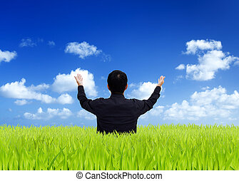 Man stretching out his hand on a green field with blue sky