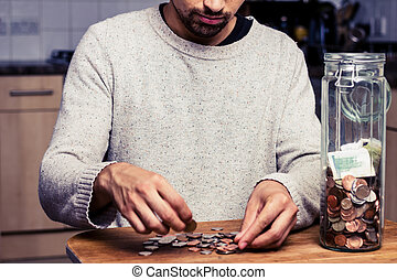 Man counting his money in kitchen