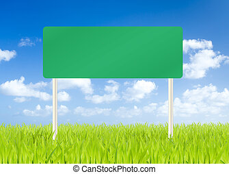 Blank road sign on green grass and blue sky background