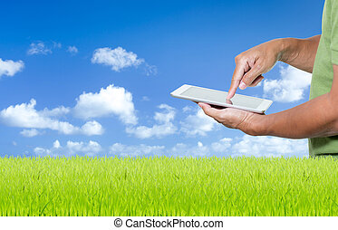 Man working with digital tablet on green grass and blue sky background