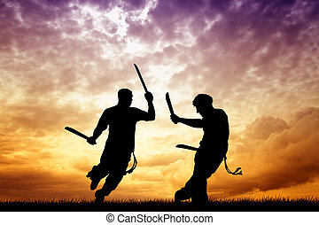 capoeira with swords at sunset