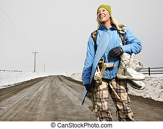 Woman going snowboarding. - Young woman in winter clothes...