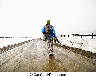 Woman carrying snowboard - Young woman in winter clothes...