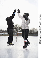 Hockey players high fiving - Two boys in ice hockey uniforms...