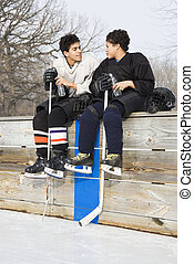 Ice hockey players - Two boys in ice hockey uniforms sitting...