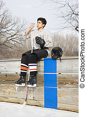Hockey boy drinking water. - Boy in ice hockey uniform...