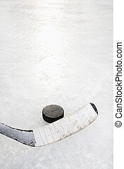 Hockey stick and puck. - Close up of ice hockey stick on ice...
