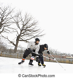 Boys playing winter sport - Two boys in ice hockey uniforms...