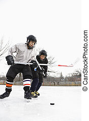Ice hockey players - Two boys in ice hockey uniforms playing...