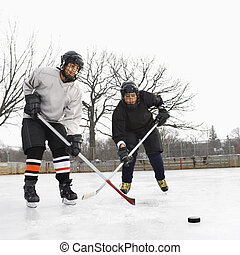 Boys playing ice hockey - Two boys in ice hockey uniforms...