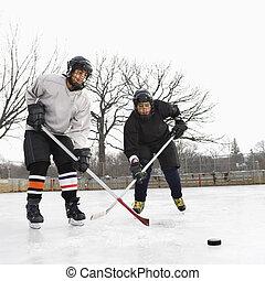 Boys playing ice hockey. - Two boys in ice hockey uniforms...