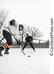 Boys playing ice hockey. - Two boys in ice hockey uniforms...