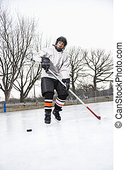 Boy playing ice hockey. - Boy in ice hockey uniform skating...