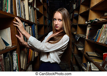 Beautiful woman choosing the book in library.