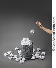 Bad ideas - Hand throwing a crumpled paper into a waste...