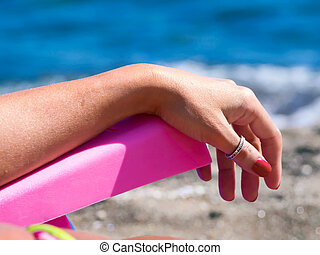woman relaxes on a deck chair, beach, facing the sea - woman...