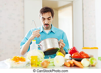 man with pan in domestic kitchen