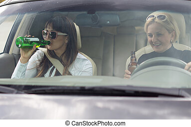 Women partying and drinking while driving - Two attractive...
