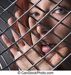 Woman through metal pattern. - Pretty redhead young woman...
