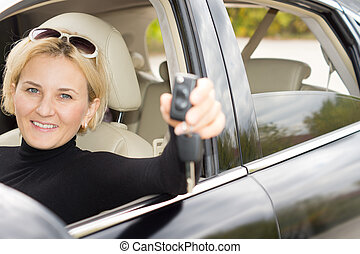 Smiling happy woman driver with a new car holding the keys...