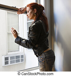 Woman looking out window. - Pretty redhead young woman...