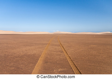 Tire tracks through the desert sand dunes in southern...