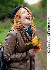 Portrait of a beautiful redhair girl in the autumn park...