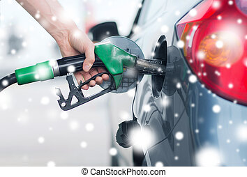 man pumping gasoline fuel in car at gas station -...
