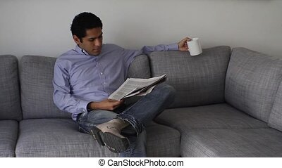 Handsome businessman reading newspaper on coffee break