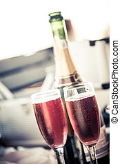 some bubbly - and soft image of two glasses filled with pink...