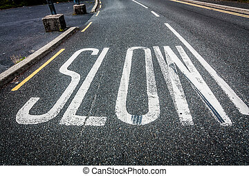 Slow written on the road - Worded marking SLOW painted on...