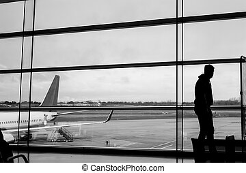 Silhouette of a passenger in an airport gate