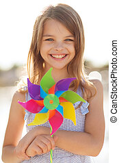 happy girl with colorful pinwheel toy - summer holidays,...