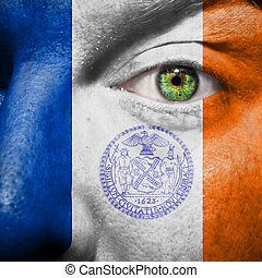New York city flag painted on a man's face with a green eye...