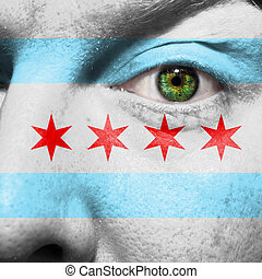 Chicago city flag painted on a mans face with a green eye to...