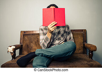 man hiding his face behind book on old sofa
