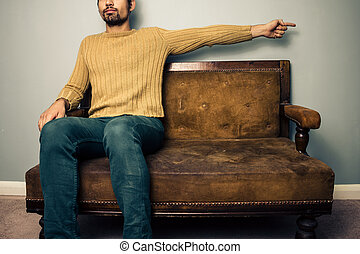 Young man on sofa pointing right