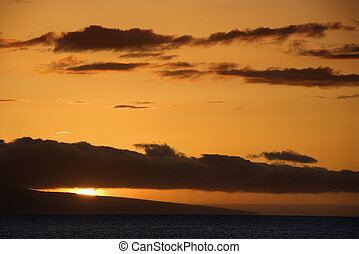Pacific ocean sunset - Orange sunset behind island in...