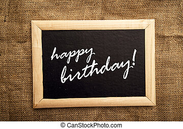 Happy birthday note on black messageboard