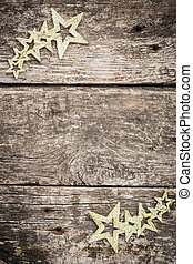 Gold Christmas tree decorations on grunge wood background....