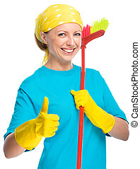 Young woman as a cleaning maid holding broom and showing...