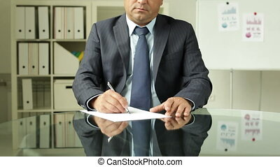 Important document - Tilt of a businessman signing some...