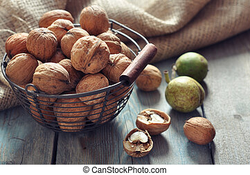 Walnuts - Whole and chopped walnuts in basket on old wooden...