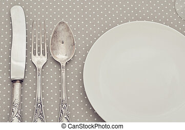 Cutlery - White plate, fork, spoon and knife on light polka...