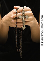 Religious rosary. - Woman holding rosary with crucifix.